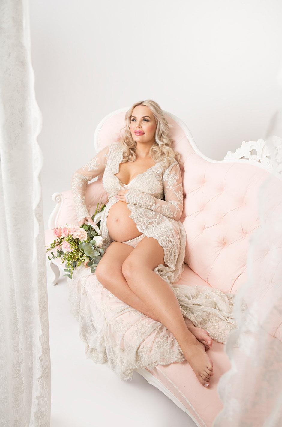 Gravidfotografering i rosa sofa
