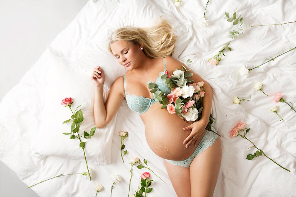 Blomster og gravid kvinne i seng.